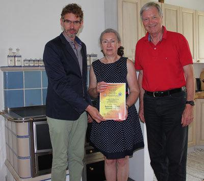 Hafnermeister Günter Wittek überreicht Hedwig und Martin Leitl das UZ-Zertifikat zum neuen Kachelherd mit Umweltzeichen.