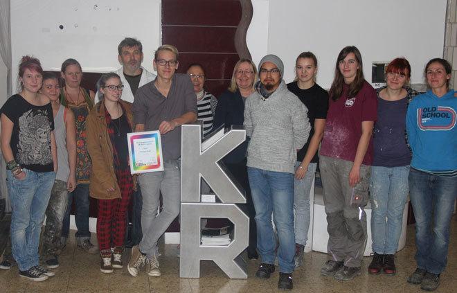 Preisausschreiben-Gewinner kann sich im Kreise seiner Schulkollegen der Keramikachschule Soob ganz entspannt auf seinen Dispenser mit den beiden Buchstzaben K und R stützen.
